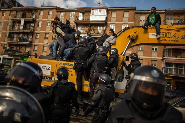 Riot Police remove a housing rights activists who claimed a bulldozer as they triy to stop Luisa Gracia Gonzalez and her family's eviction and the demolition of their house by a forced expropriation in Madrid, Spain, Friday, Feb. 27, 2015. Madrid authorities say 11 people were arrested after several dozen protesters clashed with police who were carrying out an eviction order.A city spokeswoman said seven people were arrested for throwing gasoline at police officers, though she said the fuel was not set alight. The official spoke on condition of anonymity in keeping with city hall rules.Evictions in Spain have soared since the country's economic crisis began in 2008 and increasing numbers of people were unable to meet mortgage payments. Protesters regularly try to prevent evictions, but Friday's clash was particularly tense after a campaign to keep the family in its home. The house was expropriated for demolition as part of new urban project. Some 30 protesters tried to stop it, accusing authorities of real estate speculation. (AP Photo/Andres Kudacki)